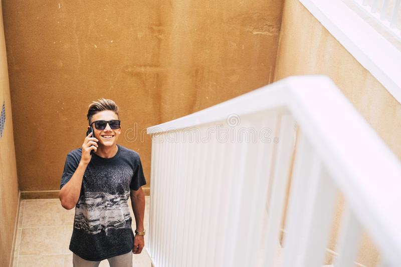 Attractive teenager waiting at someone on the stairs while his calling and talking with someone with his phone - walking and royalty free stock photo