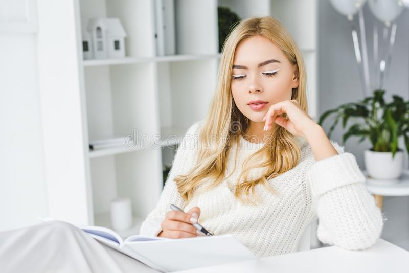 attractive thoughtful businesswoman in white clothes stock photo
