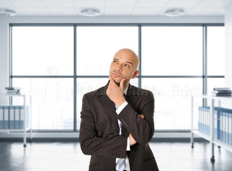 Attractive thoughtful and pensive Latin businessman in suit and tie thinking and considering ideas royalty free stock image