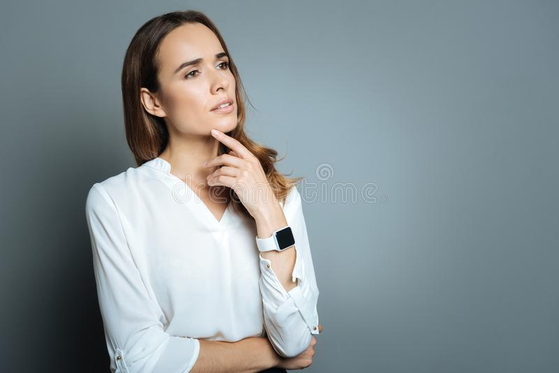 Attractive thoughtful woman pressing a finger to her chin royalty free stock photography