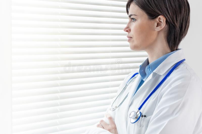 Attractive thoughtful young female doctor or nurse. Standing staring out of a high key window with louver blinds in a close up profile portrait royalty free stock photography
