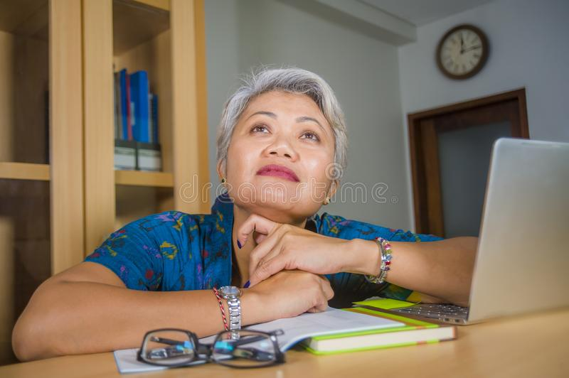 Attractive and tired middle aged Asian woman working at laptop computer desk confident daydreaming absent minded thinking about royalty free stock photos