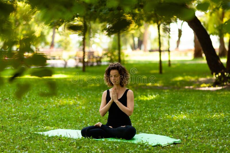 Attractive and tranquil woman sits in lotus position under tree. Yoga and meditation, concentration and relaxation, unity with royalty free stock photo