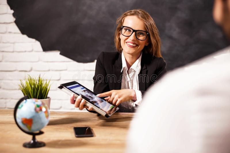 Travel Agent Proposing Hot Tours. Attractive travel agent sitting at office with client and proposing hot tours to them royalty free stock photo