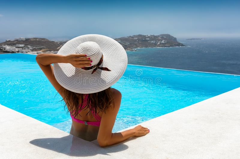 Attractive traveller woman relaxes in a pool stock images
