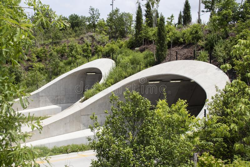 Attractive tunnels over highway in Tulsa Oklahoma near park and Arkansas River with many young trees supported as they grow and stock photos