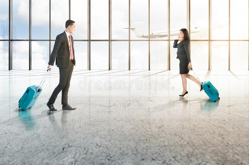 Attractive two asian business people with mobile phone and blue suitcases walking on the airport hall stock photos
