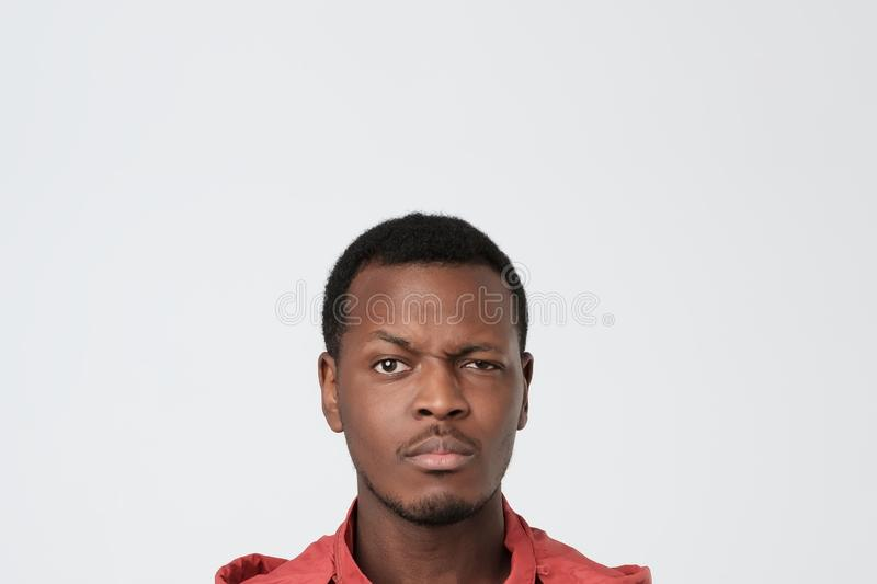 Attractive unhappy black young man over white background stock photos