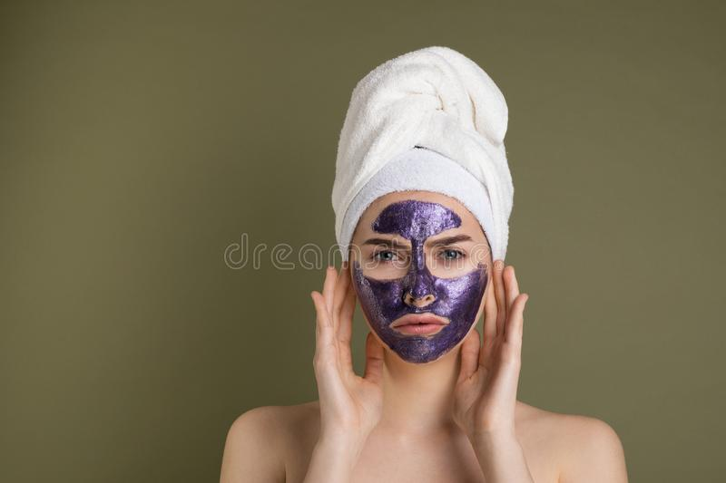 Attractive unhappy young woman with purple face mask and shower towel on her head. Touching her face looking away on green background royalty free stock photography