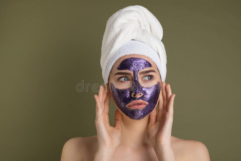 Attractive unhappy young woman with purple face mask and shower towel on her head. Touching her face looking away on green background royalty free stock photo