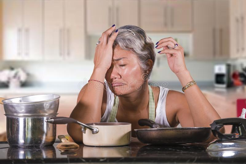 Attractive upset and stressed woman 40s to 50s tired and unhappy at home kitchen doing housework and boring housework feeling royalty free stock images