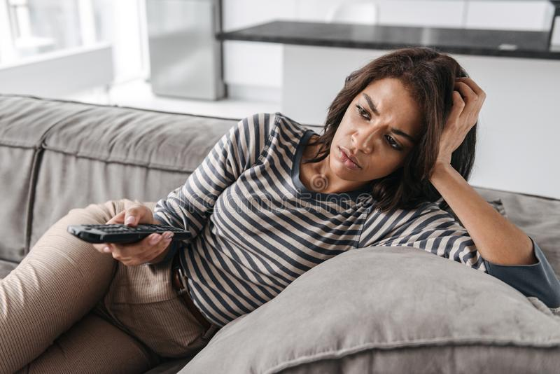 Attractive young afro american woman. Attractive upset young afro american woman sitting on a couch at home, watching TV, holding remote control royalty free stock image