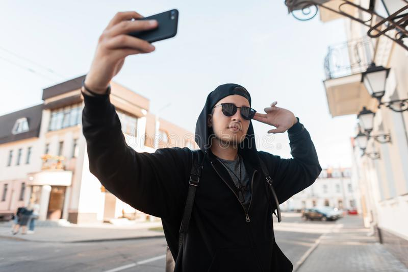 Attractive urban young hipster man in black fashionable clothes in a trendy cap in sunglasses walks through the city. And takes a selfie on the phone. Handsome royalty free stock photography