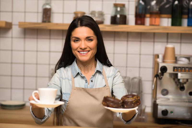 Waitress holding chocolate doughnuts. Attractive waitress holding delicious chocolate doughnuts with cup of coffee and smiling at camera stock photography