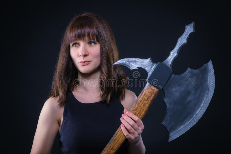 Attractive warrior girl with a battle ax in his hands stock images