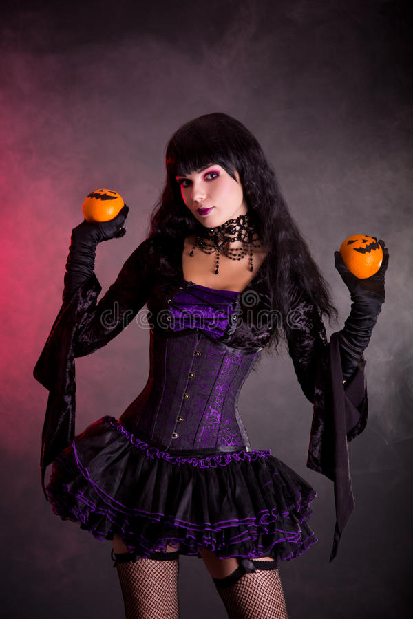 Attractive witch in purple gothic Halloween costume. Holding Jack-o-lantern style oranges royalty free stock photos