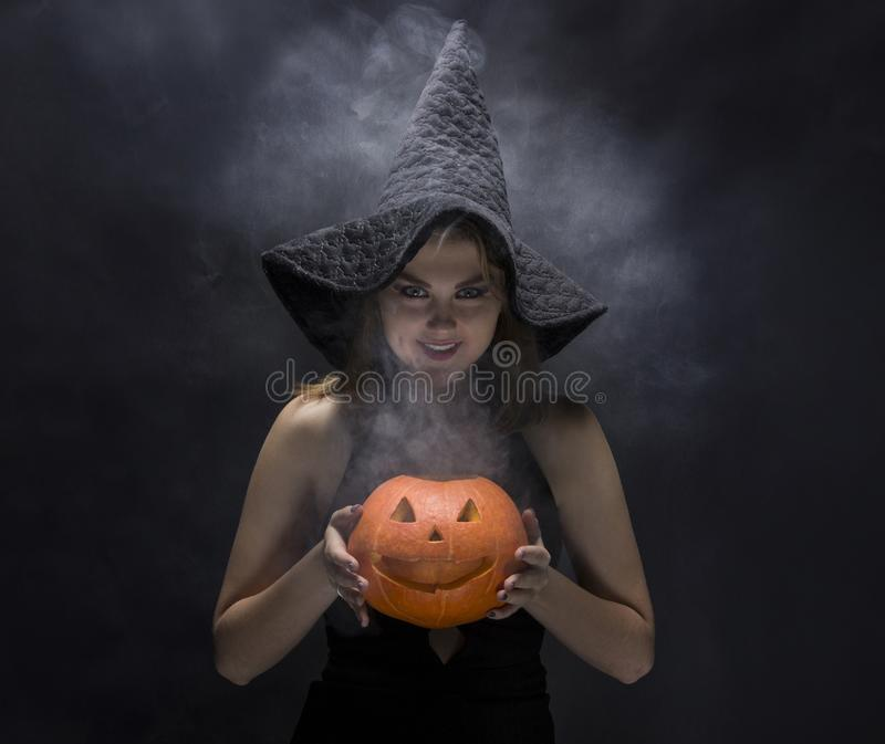 Attractive witch with smoky pumpkin in her hands royalty free stock photos