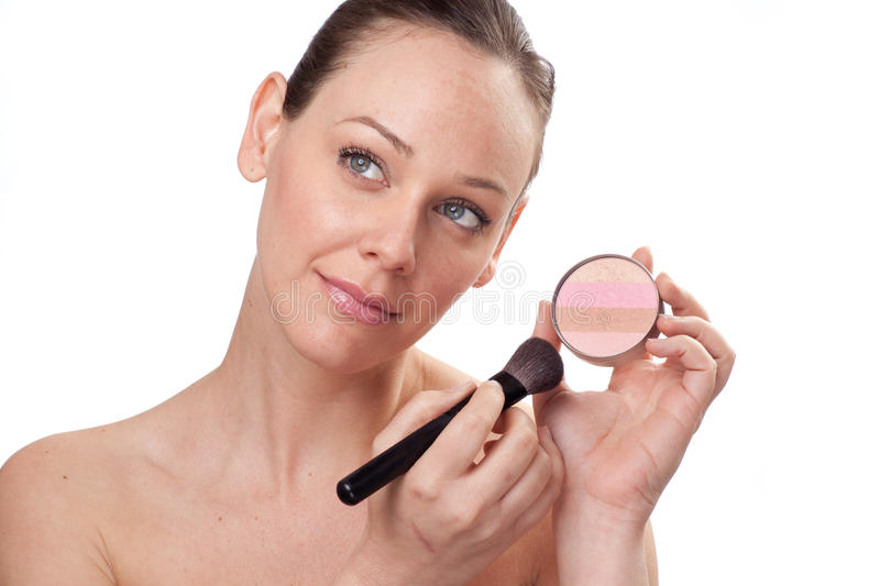 Attractive woman applying blusher