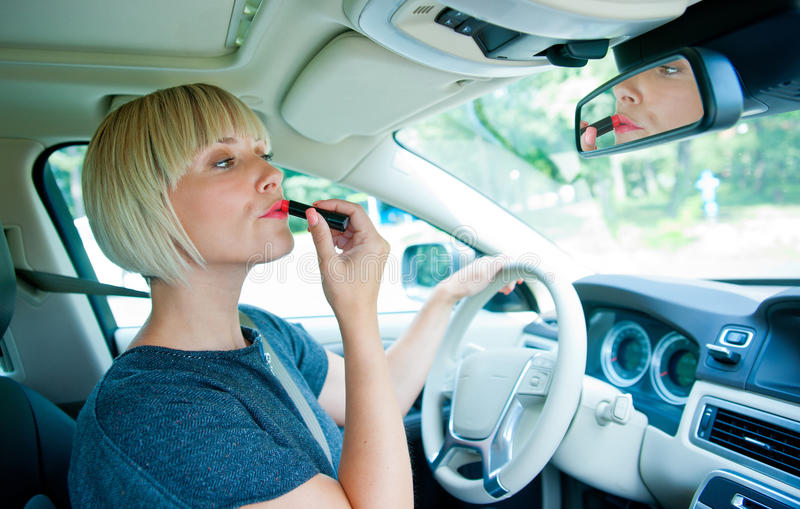 Attractive woman applying make up in her car stock photo