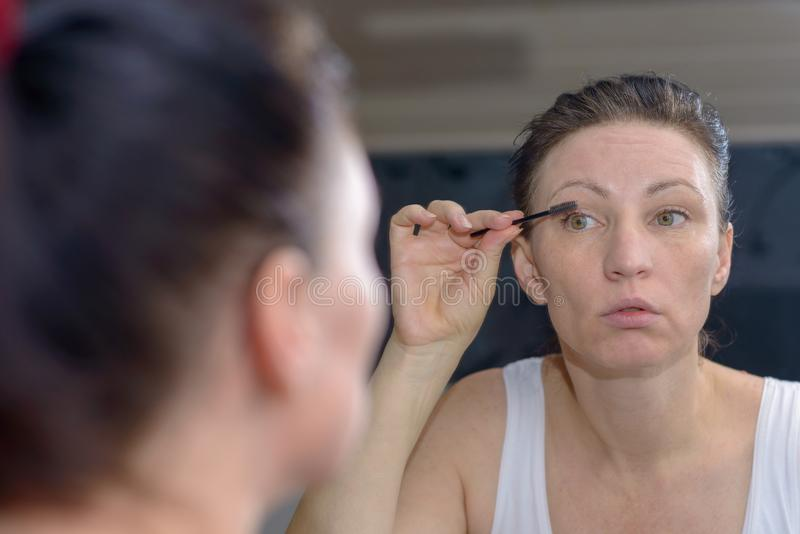 Attractive woman applying mascara to her lashes royalty free stock photo