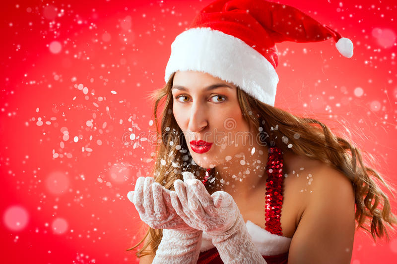 Attractive woman as Santa Claus blowing snow. Attractive young woman in Santa Claus costume blowing snow flakes on isolated red background Xmas celebration stock image