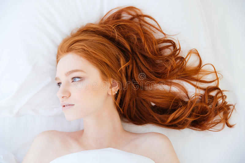 Attractive woman with beautiful long red hair lying in bed stock image