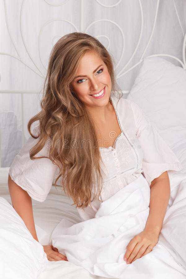 Attractive woman in the bed stock photography