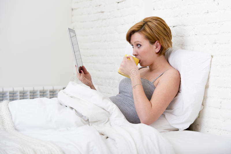 Attractive woman on bed using digital tablet pad reading morning online news in internet having coffee royalty free stock photography