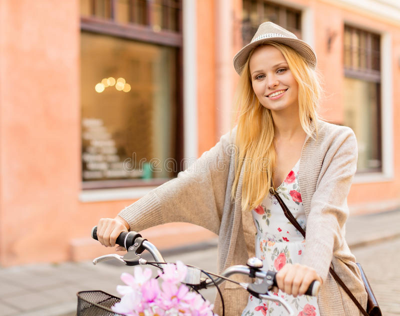 Attractive woman with bicycle in the city stock photography