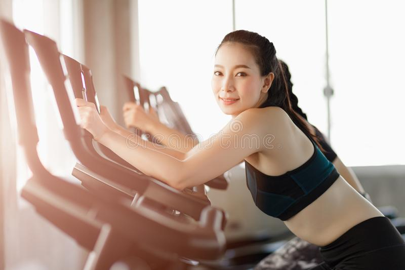 Attractive woman biking in the gym, exercising legs doing cardio workout cycling bikes. stock photography