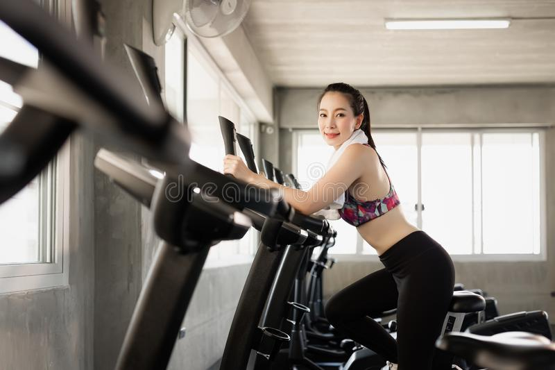 Attractive woman biking in the gym, exercising legs doing cardio workout cycling bikes. Fitness club with training exercise bikes. stock image