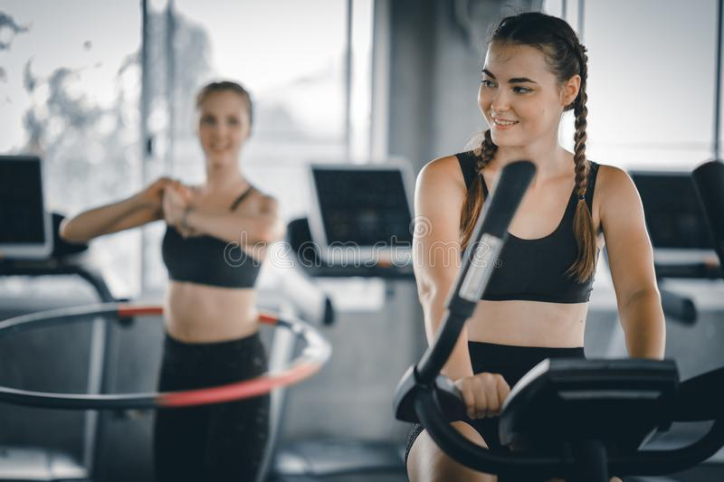 Attractive woman biking in the gym, exercising legs doing cardio workout cycling bikes. Fitness club with training exercise bikes stock image