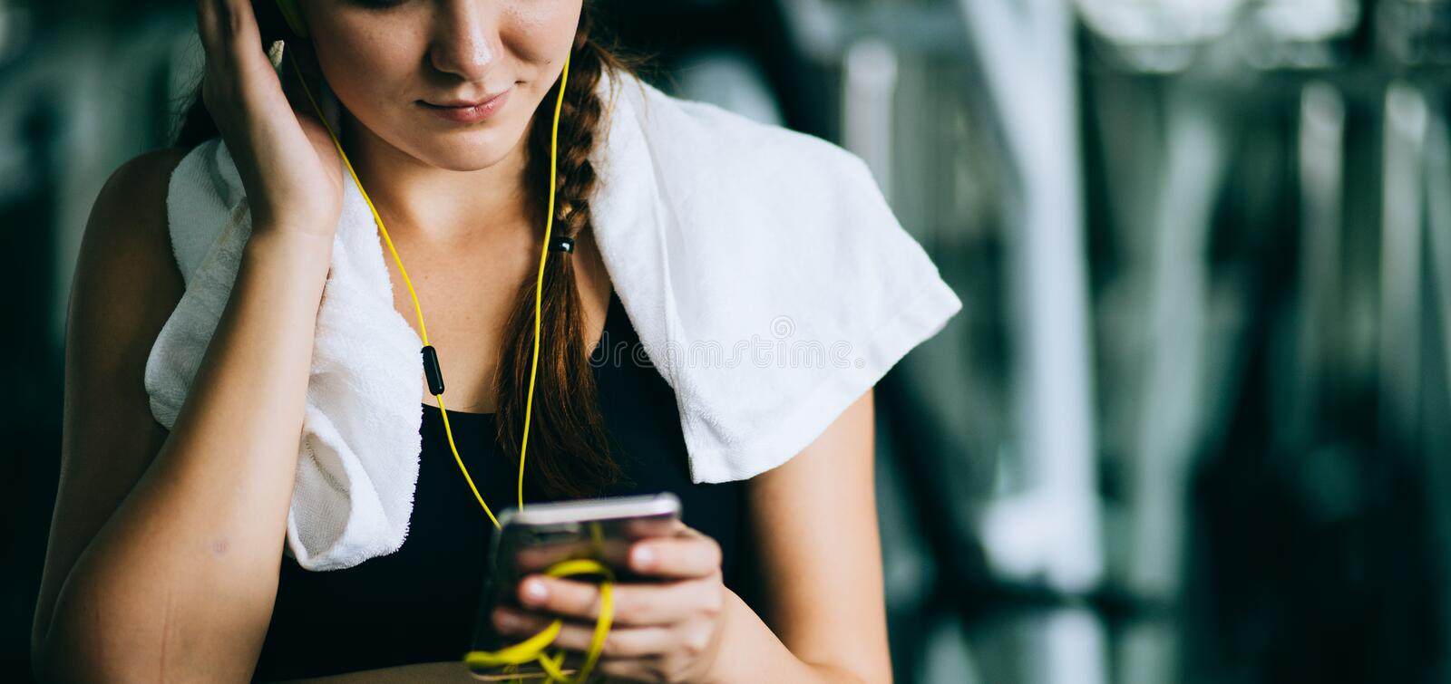 Attractive woman biking in the gym, exercising legs doing cardio workout cycling bikes. royalty free stock image
