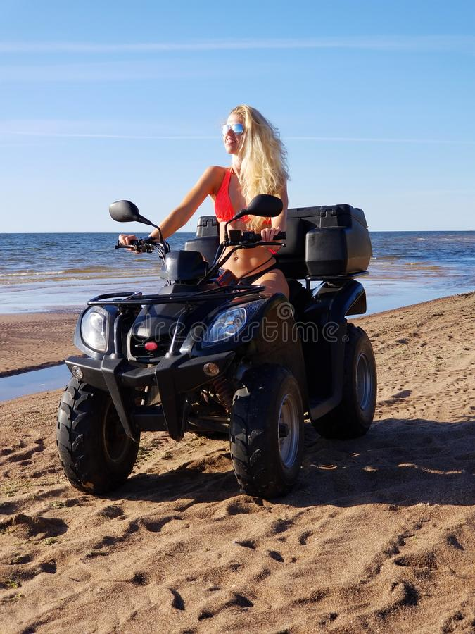 Attractive woman in bikini with long blonde hair is sitting on the quad bike, sunny day royalty free stock photos