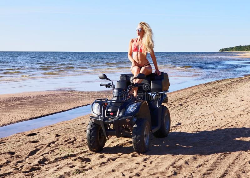 Attractive woman in bikini with long blonde hair is sitting on the quad bike, sunny day stock photos