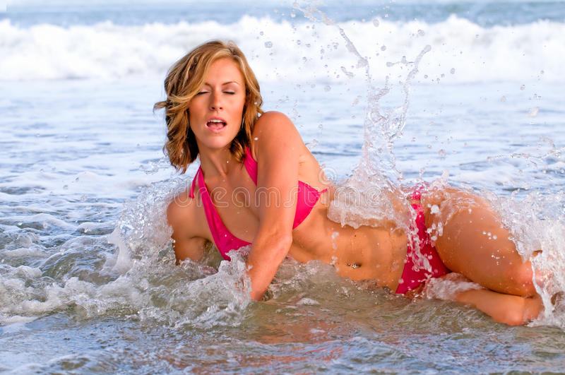 Attractive woman in bikini splashed by wave royalty free stock photography