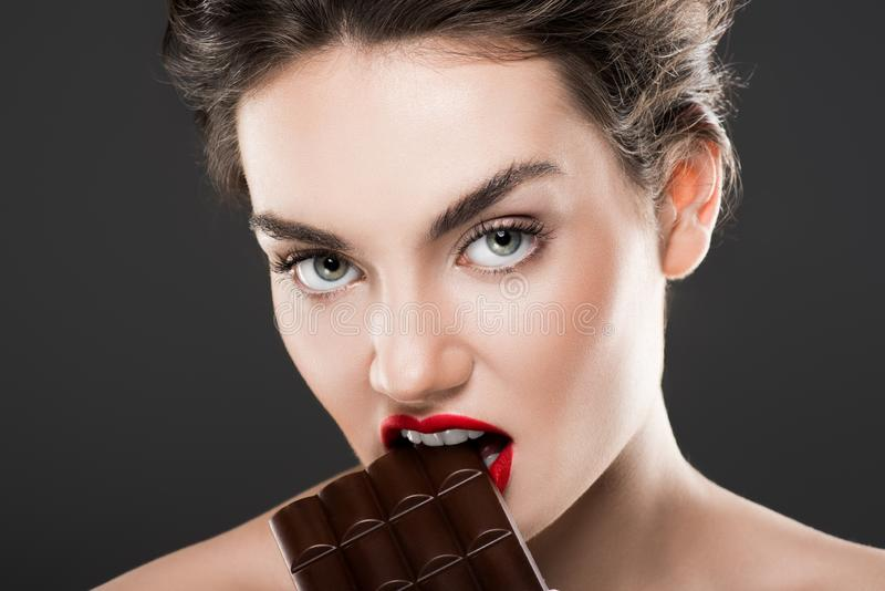 attractive woman biting chocolate bar stock photo