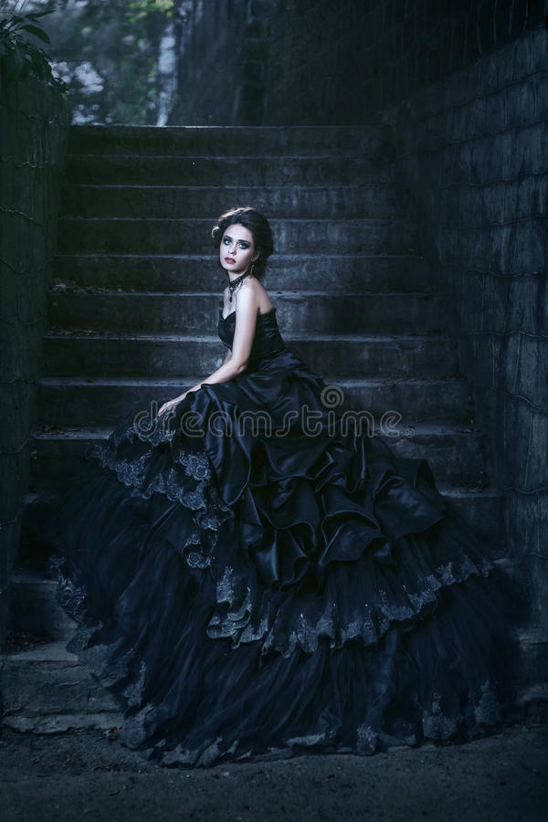 Attractive woman in black dress. Near stone wall stock photography
