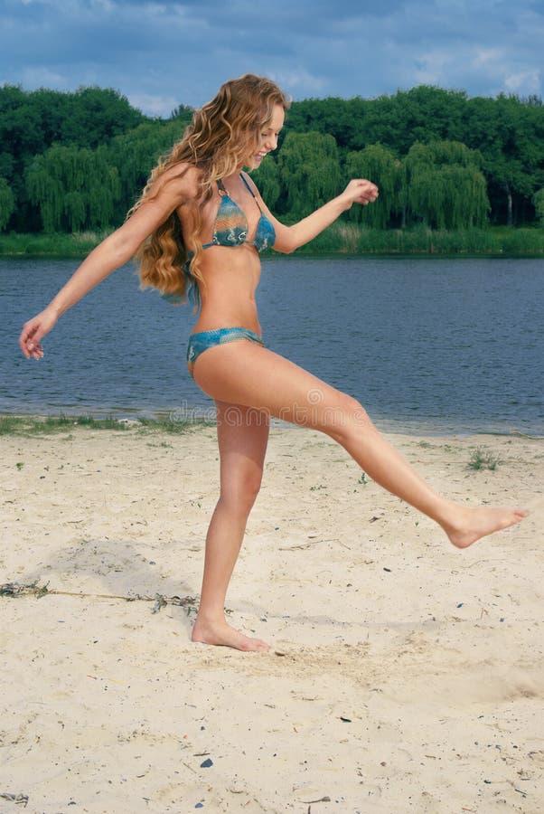 Attractive woman in blue bikini on river beach royalty free stock photo