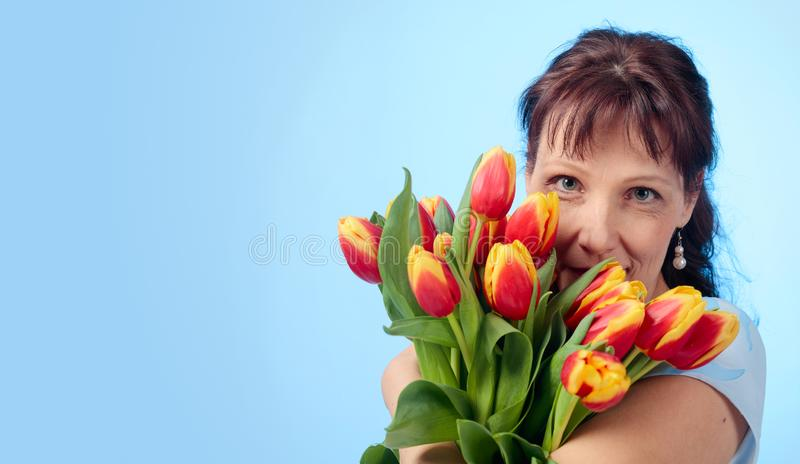 Attractive woman in blue dress with a bouquet of red and yellow tulips. Attractive middle-aged woman in blue dress with a bouquet of red and yellow tulips. Blue stock photography