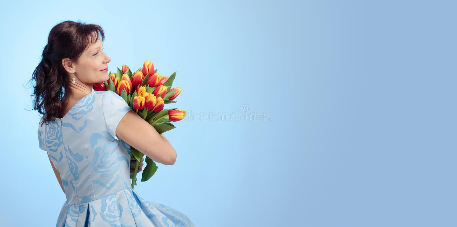 Attractive woman in blue dress with a bouquet of red and yellow tulips. Attractive middle-aged woman in blue dress with a bouquet of red and yellow tulips. Blue stock photos