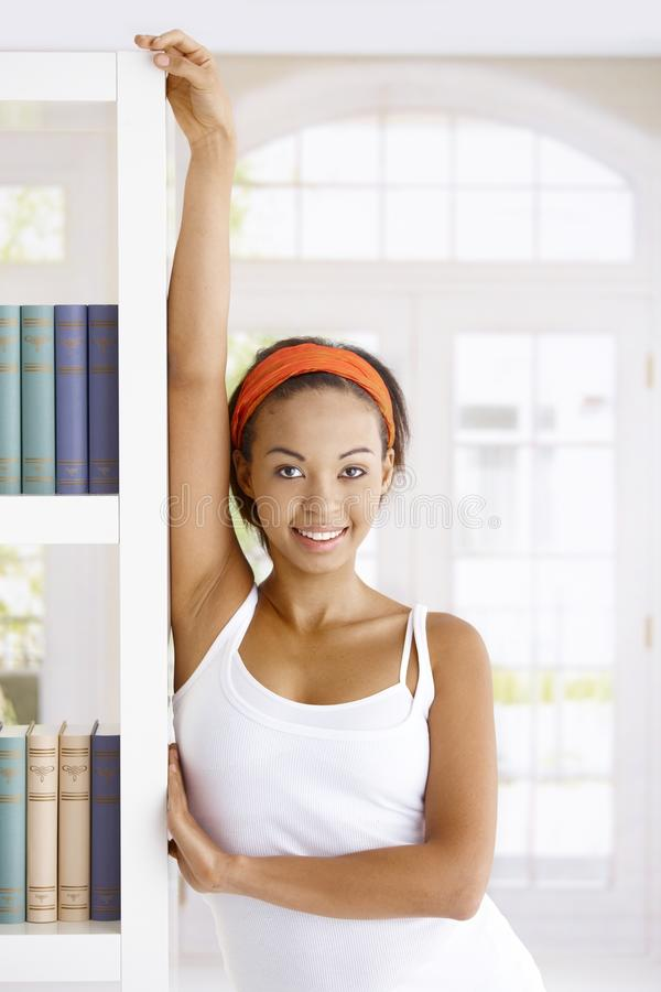 Attractive woman at book shelf. Attractive woman posing at book shelf at home, smiling at camera royalty free stock image