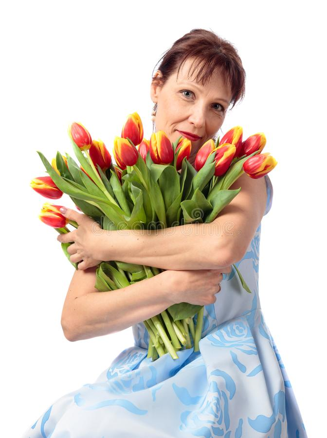 Attractive woman with a bouquet of red and yellow tulips. Attractive middle-aged woman with a bouquet of red and yellow tulips.Isolated on white background royalty free stock photos