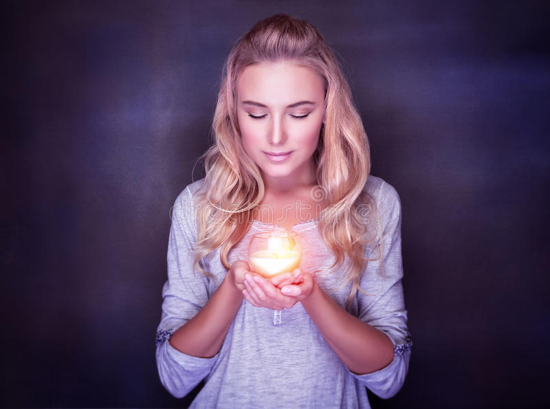 Attractive woman with candle. On dark background, calm girl with closed eyes praying, Christmas holidays concept royalty free stock photos