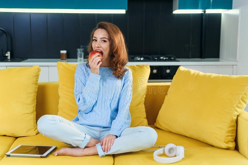 Attractive woman in casual clothes eating fresh juicy red apple while sitting on comfortable yellow couch in the royalty free stock photo