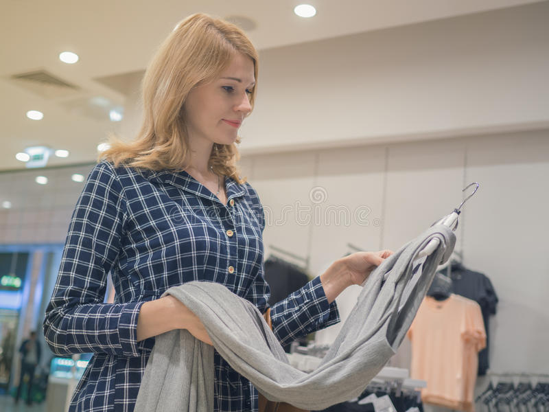 Attractive woman chooses clothes in a shop. The concept of shopping, buy fashion clothes in the store. royalty free stock images