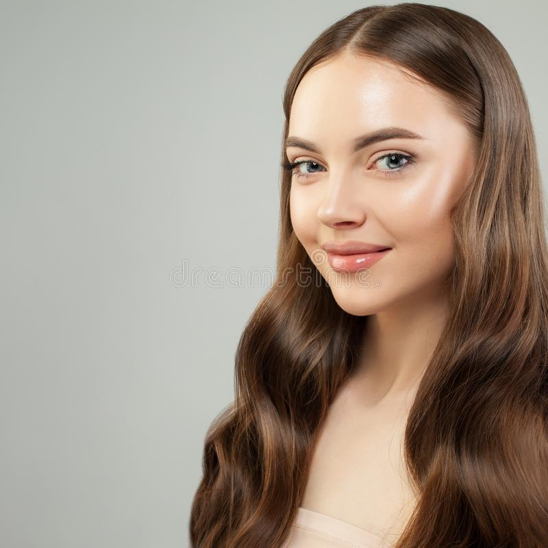Attractive woman with clear skin and healthy curly brown hair smiling. Beautiful face close up. Skin care and hair care concept royalty free stock photos