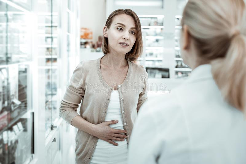 Attractive woman complaining to the druggist of her stomach ache. Stomach ache. Attractive women with dark haircut complaining to the female druggist wearing a stock photography
