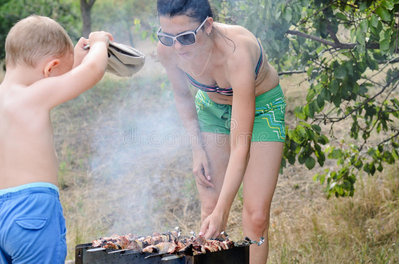 Attractive woman cooking over a barbecue royalty free stock photography