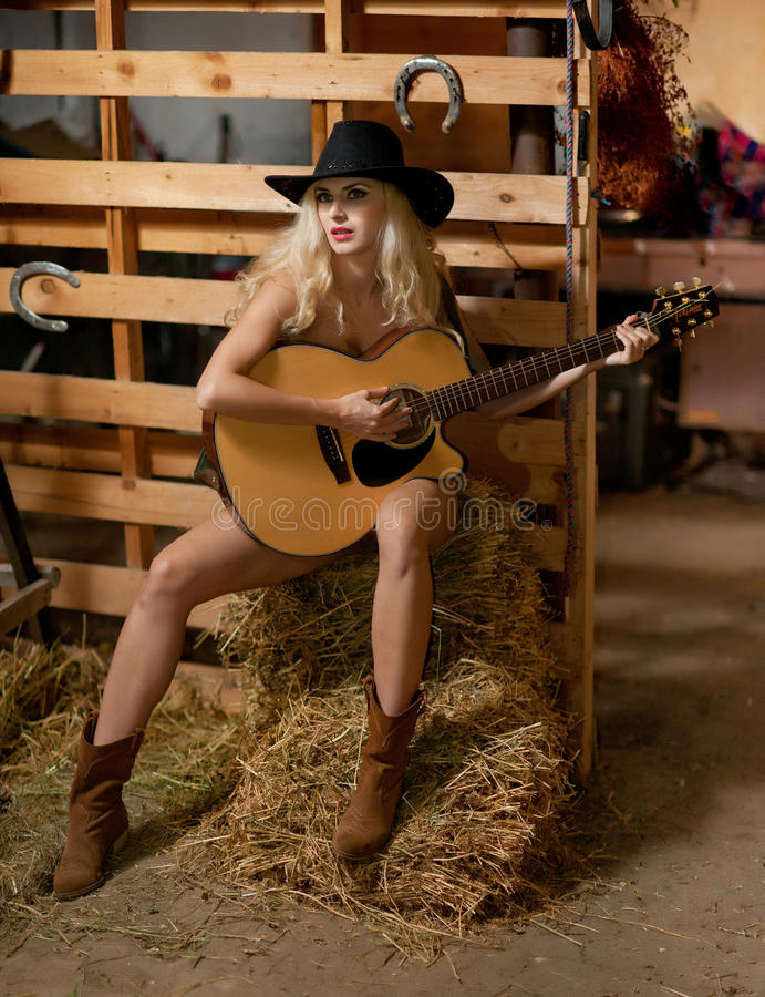 Attractive woman with country look, indoors shot, american country style. Blonde girl with black cowboy hat and guitar royalty free stock photos